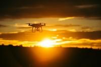 Silhouet van een drone tegen een zonsondergang